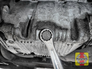 Illustration of step: With an oil catchment tray in position, use a 19mm spanner or socket to carefully remove the sump plug and fully drain the oil - step 3