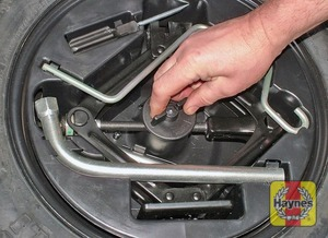 Illustration of step:  Unscrew the retaining bolt, and lift out the tool container, followed by the spare wheel - Changing the wheel - step 3