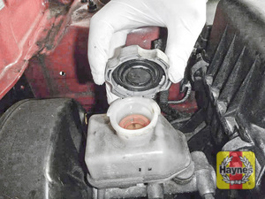 Illustration of step: If the level needs topping up - WEARING GLOVES - carefully open the cap, have a paper towel ready to catch any drips as brake fluid is corrosive - step 4