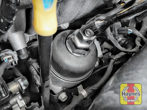 Illustration of step: Using a 27mm filter wrench socket, fit the tool securely onto the oil filter housing - step 2