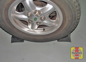 Illustration of step:  Place the chocks behind and in front of the wheel diagonally opposite to the one to be removed - Changing the wheel - step 5