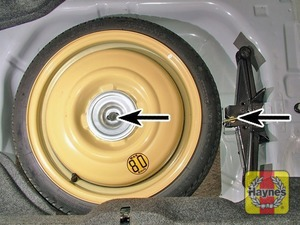 Illustration of step:  Unscrew the retaining bolts/nuts, and lift out the tools, followed by the spare wheel - step 4