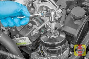 Illustration of step: Using a specific filter wrench socket, fit the tool securely onto the oil filter housing - step 3