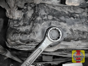 Illustration of step: Use a 22mm spanner or socket to carefully remove the sump plug and fully drain the oil - step 3