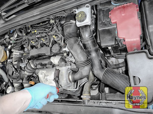 Illustration of step: To gain access to the oil filter cartridge, firstly undo the two circular clips on the air intake - use a screwdriver - step 1