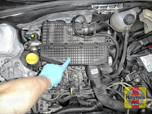 Illustration of step: The air is filter located underneath the engine cover, using both hands, pop off the engine cover and place to one side - step 1