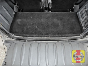 Illustration of step: The engine is at the base of the rear cargo area, under the carpet - step 1