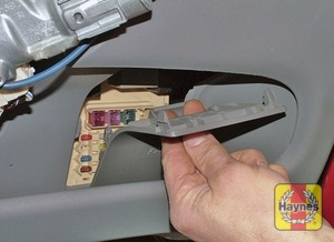 Illustration of step: Unclip the panel from the driver's side storage tray to access the main fusebox - step 1