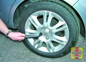 Illustration of step:  Use the special tool or screwdriver provided to pull the wheel trim from the wheel or wheel bolts, then slacken each wheel bolt by half a turn - step 4
