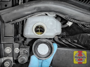 Illustration of step: If the level needs topping up -WEARING GLOVES - carefully open the cap, have a paper towel ready to catch any drips because brake fluid is corrosive - step 3