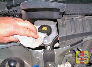 Illustration of step:  If topping-up is necessary, first lift the plastic cover then wipe clean the area around the filler cap to prevent dirt entering the hydraulic system - Safety first! - step 27