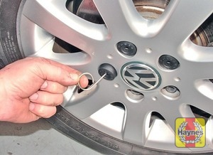 Illustration of step:  On alloy wheels, use the plastic puller from the tool kit to remove the cover from each wheel bolt, including the anti-theft bolt - step 5