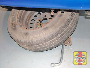 Illustration of step:  Lower the folding bracket to the ground, then lift the spare wheel out of the folding bracket - step 8