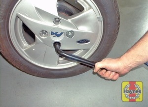 Illustration of step:  On models where the wheel nuts are not visible, use the blade end of the wheel brace to prise off the wheel trim - step 4