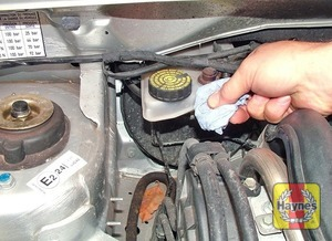 Illustration of step:  If topping-up is necessary, first wipe the area around the filler cap with a clean rag before removing the cap -  	Safety first! - step 48