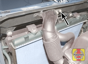 Illustration of step:  Undo the nut (arrowed) securing the air intake duct to the front body panel – later models  - 1.6 litre models and post-September 2002 1.4 litre models - step 12