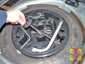 Illustration of step:  Lift the floor panel, unscrew the plastic nut, and lift out the tool holder - Changing the wheel - step 7