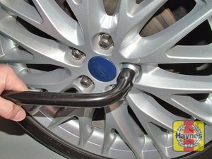 Illustration of step:  Slacken each wheel nut by a half turn, using the wheel brace - step 4