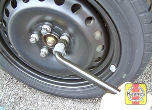 Illustration of step:  Lower the car to the ground and fully tighten the wheel nuts, then refit the wheel trim or centre cover, as applicable - Changing the wheel - step 8