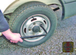 Illustration of step:  Where applicable, prise off the wheel nut covers or wheel trim, using the flat end of the wheelbrace, for access to the wheel nuts - step 7