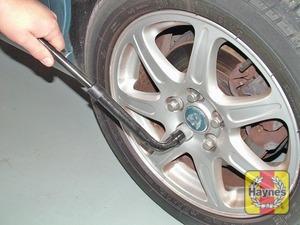 Illustration of step:  Slacken each wheel nut by a half turn, using the wheel brace - Changing the wheel - step 5