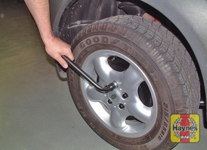 Illustration of step:  Before raising the vehicle, prise off the wheel nut cover (where fitted), and use the wheel nut brace to slacken each of the wheel nuts half a turn - step 5