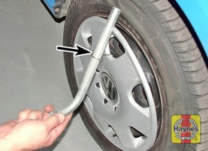 Illustration of step:  On steel wheels, use the wire hook and wheel brace to remove the wheel trim from the wheel - step 4