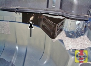 Illustration of step:  Undo the wing nut and remove the wheel chock from the inside of the rear panel - step 4