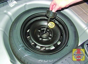 Illustration of step:  Lift the floor covering and unscrew the spare wheel clamp bolt - step 1