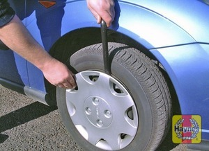 Illustration of step:  Where applicable, using the flat end of the wheelbrace, prise off the wheel trim or centre cover for access to the wheel nuts - Changing the wheel - step 4