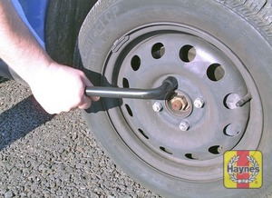 Illustration of step:  Slacken each wheel nut by a half turn, using the wheelbrace - Changing the wheel - step 5