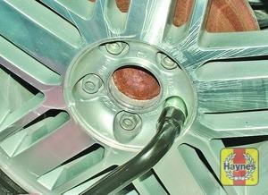 Illustration of step:  Slacken each wheel nut by a half turn, using the wheel brace - Changing the wheel - step 4