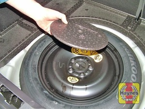 Illustration of step:  The spare wheel and tools are stored under the floor in the luggage compartment - step 2