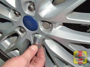Illustration of step:  Where applicable, using the flat end of the wheel brace, prise off the wheel trim or centre cover for access to the wheel nuts - step 3