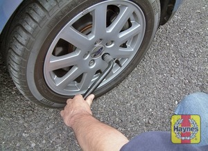 Illustration of step:  If necessary, use the flat end of the wheelbrace to prise off the centre cover or wheel trim to access the wheel nuts - Changing the wheel - step 4