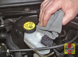 Illustration of step:  If topping-up is necessary, first wipe clean the area around the filler cap to prevent dirt entering the hydraulic system, then unscrew and remove the reservoir cap - Safety first! - step 35