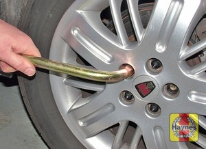 Illustration of step:  Prise off the wheel trim or wheel centre cap from the punctured wheel, using the end of the wheelbrace or the hooked tool - step 4
