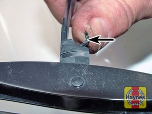 Illustration of step:  To remove a front wiper blade, pull the arm away from the screen, turn the blade 90° to the arm, depress the clip and slide the blade down the arm - step 2