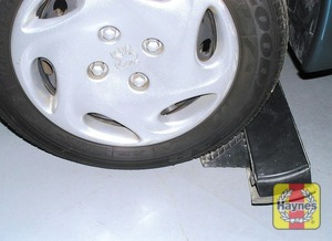 Illustration of step: Use the jack holder to chock the wheel diagonally opposite the one being removed - step 5