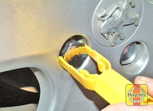 Illustration of step:  On models where anti-theft wheel bolts are fitted (alloy wheels), pull off the plastic cover using the yellow plastic tool in the tool kit  - step 5