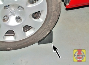 Illustration of step:  Place the chock (arrowed) provided in the vehicle tool kit against the wheel diagonally opposite the wheel to be removed, or use a stone/rock to stop the car rolling - step 7