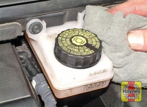 Illustration of step:  If topping-up is necessary, first wipe clean the area around the filler cap with a clean cloth, then unscrew the cap and remove it along with the rubber diaphragm - Before you start - step 18