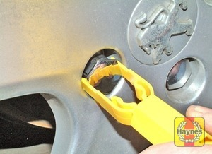 Illustration of step:  On models where anti-theft wheel bolts are fitted, pull off the plastic cover using the plastic tool in the tool kit  - step 5