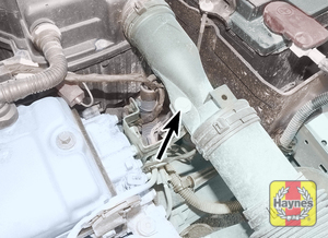 Illustration of step:  Undo the bolt (arrowed) securing the air intake duct to the support bracket – early 1 - Pre-September 2002 1.4 litre models - step 5