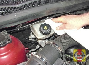 Illustration of step:  If topping-up is necessary, first wipe clean the area around the filler cap to prevent dirt entering the hydraulic system -  Safety first! - step 26