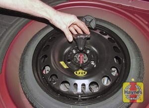 Illustration of step:  Lift the floor covering and unscrew the spare wheel clamp nut - step 2