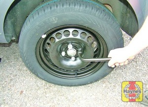 Illustration of step:  Fit the spare wheel and tighten the bolts moderately with the wheel brace - step 7