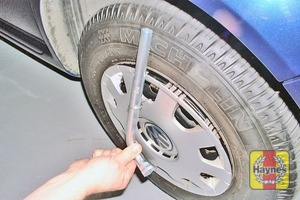 Illustration of step:  Use the wire hook and wheel brace to remove the wheel trim - step 6