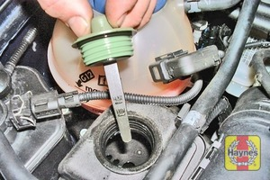Illustration of step:  Unscrew the cap from the hydraulic fluid reservoir, and wipe clean the integral dipstick with a clean cloth  - Power steering fluid level checks - step 38