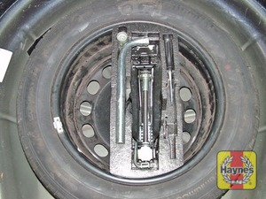 Illustration of step:  The spare wheel and tools are stored in the luggage compartment, lift up the floor panel/carpet - step 2